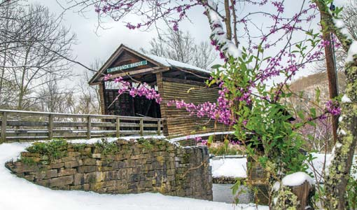 Humpback Bridge in early spring with snow and redbuds